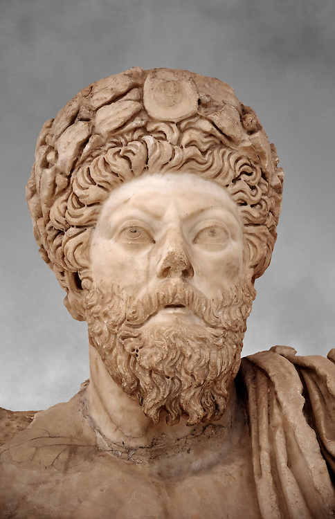 Roman sculpture of the Emperor Marcus Aurelius, excavated from Bulla Regia Theatre, sculpted circa late second century. The Bardo National Museum, Tunis. Against a grey art background. .<br /> <br /> If you prefer to buy from our ALAMY STOCK LIBRARY page at https://www.alamy.com/portfolio/paul-williams-funkystock/greco-roman-sculptures.html . Type -    BARDO    - into LOWER SEARCH WITHIN GALLERY box - Refine search by adding a subject, place, background colour, museum etc.<br /> <br /> Visit our CLASSICAL WORLD HISTORIC SITES PHOTO COLLECTIONS for more photos to download or buy as wall art prints https://funkystock.photoshelter.com/gallery-collection/The-Romans-Art-Artefacts-Antiquities-Historic-Sites-Pictures-Images/C0000r2uLJJo9_s0c