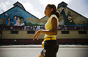 A girl walks past a mural depicting Fidel Castro and a Cuban family in Santiago, Cuba on Wednesday July 9, 2008.