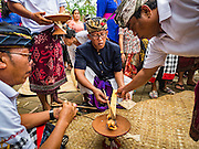 16 JULY 2016 - UBUD, BALI, INDONESIA:  People with pray over a flame taken from the funeral pyre burning a member of their family. Local people in Ubud exhumed the remains of family members and burned their remains in a mass cremation ceremony Wednesday. Almost 100 people were cremated and laid to rest in the largest mass cremation in Bali in years this week. Most of the people on Bali are Hindus. Traditional cremations in Bali are very expensive, so communities usually hold one mass cremation approximately every five years. The cremation in Ubud concluded Saturday, with a large community ceremony.    PHOTO BY JACK KURTZ