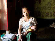 A young Hmong ethnic minority woman breastfeeds her 2 month old baby inbetween making textile products to sell at the Luang Prabang night market, Ban Na Ouane village, Luang Prabang province, Lao PDR. The Hmong have recently settled in the town of Luang Prabang - a consequence of the government's efforts to suppress both the cultivation of opium poppies and slash and burn agriculture, which they have traditionally practiced, and of their own desire to take advantage of the expansion of tourism, which provides an important outlet for their crafts. These women have developed an artisanal textile industry based on their remarkable heritage.  Using their skilful embroidering and combining the sophisticated, colourful motifs that have traditionally adorned their clothing they have created aprons, tablecloths, cushion and bed covers, slippers and more which they sell to tourists at the Luang Prabang night market.