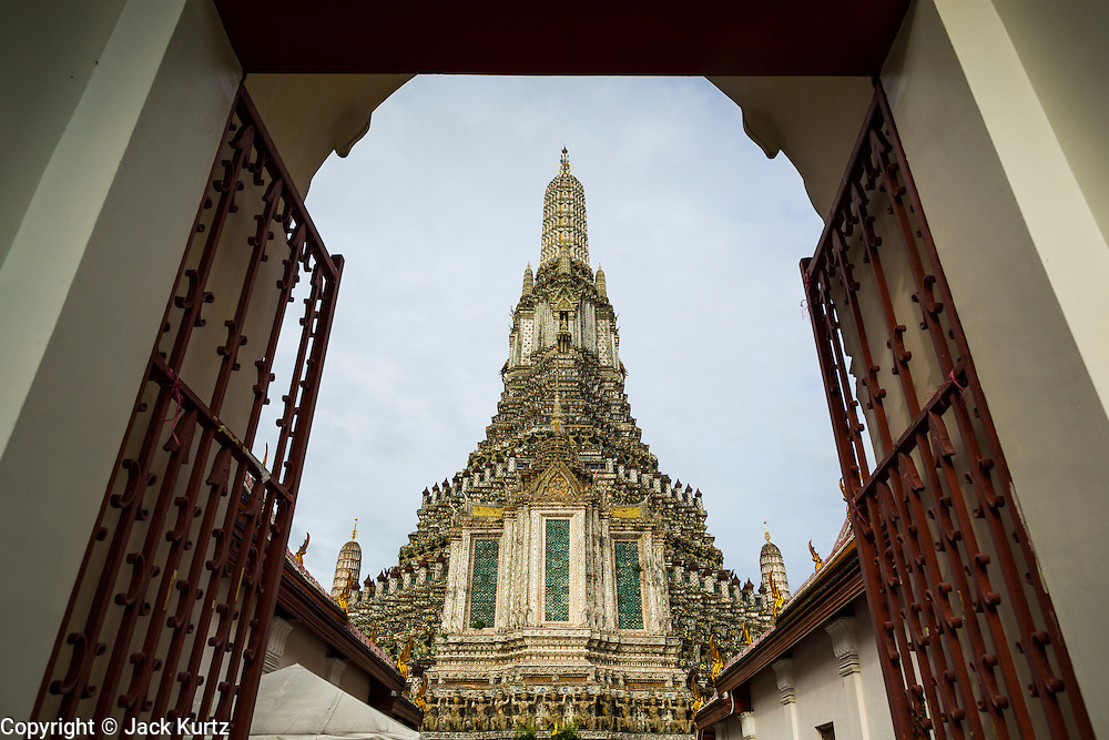 "23 SEPTEMBER 2013 - BANGKOK, THAILAND: The famous central chedi at Wat Arun framed by the gate to the temple. The full name of the temple is Wat Arunratchawararam Ratchaworamahavihara. The outstanding feature of Wat Arun is its central prang (Khmer-style tower). The world-famous stupa, known locally as Phra Prang Wat Arun, will be closed for three years to undergo repairs and renovation along with other structures in the temple compound. This will be the biggest repair and renovation work on the stupa in the last 14 years. In the past, even while large-scale work was being done, the stupa used to remain open to tourists. It may be named ""Temple of the Dawn"" because the first light of morning reflects off the surface of the temple with a pearly iridescence. The height is reported by different sources as between 66,80 meters and 86 meters. The corners are marked by 4 smaller satellite prangs. The temple was built in the days of Thailand's ancient capital of Ayutthaya and originally known as Wat Makok (The Olive Temple). King Rama IV gave the temple the present name Wat Arunratchawararam. Wat Arun officially ordained its first westerner, an American, in 2005. The central prang symbolizes Mount Meru of the Indian cosmology. The temple's distinctive silhouette is the logo of the Tourism Authority of Thailand.           PHOTO BY JACK KURTZ"