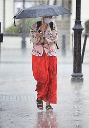 © Licensed to London News Pictures. 13/08/2020. Epsom, UK. A shopper walks through a heavy downpour in Epsom, Surrey as the UK experiences thunderstorms and heavy rainfall following days of high temperatures. Photo credit: Peter Macdiarmid/LNP
