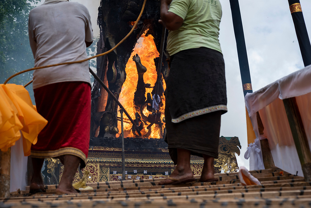Bali, Indonesia - February 13, 2017: Two men direct fire onto a body being cremated at Pura Dalem Puri Peliatan, a temple in Ubud, Bali, Indonesia.