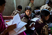 Poonam, 13, (centre) is having her homework checked by a teacher, while sitting on the floor of a classroom inside the cozy, private school she regularly attends with her older sister Jyoti, 14, since 2011, and located close to their newly built home in Oriya Basti, one of the water-contaminated colonies in Bhopal, central India, near the abandoned Union Carbide (now DOW Chemical) industrial complex, site of the infamous '1984 Gas Disaster'.