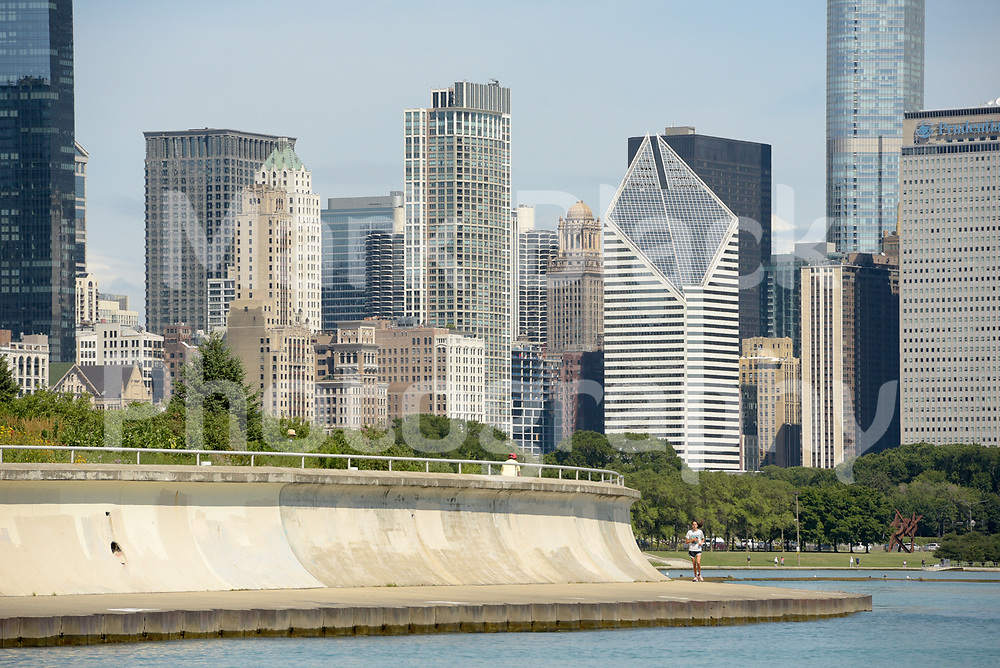 Joggers along the lakefront with the Chicago Skyline along Lake Michigan in Chicago, Illinois.<br /> Photo by Mark Black
