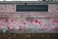 A bouquet of flowers is pictured in front of the National Covid Memorial Wall on the South Bank of the River Thames on 15th October 2021 in London, United Kingdom. The National Covid Memorial Wall is a public mural comprising thousands of red and pink hearts painted by volunteers in order to commemorate the victims of the COVID-19 pandemic in the United Kingdom.