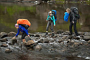 Backpackers crossing river at Loch Coirusk, Isle of Skye, Scotland