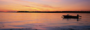 Recreation boat moored in calm water on lake at sunset.