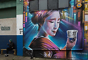 A man uses his mobile phone alongside a large mural showing a Japanese Geisha lady holding a cup of sake, outside the UKs first sake brewery, Kanpai London Sake Brewery & Taproom in Copeland Park in Peckham, on 2nd December 2019, in London, England.