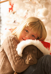 Close up of a young girl hugging a puppy wearing a Christmas hat