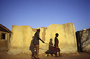 Anafo, a blind farmer is guided from his fields by a neighbour's child holding a stick. Anafo is blind due to the entirely preventable 'Rive Blindness' (Onchocerciasis) but despite his handicap, Anafo has no choice but to continue farming.
