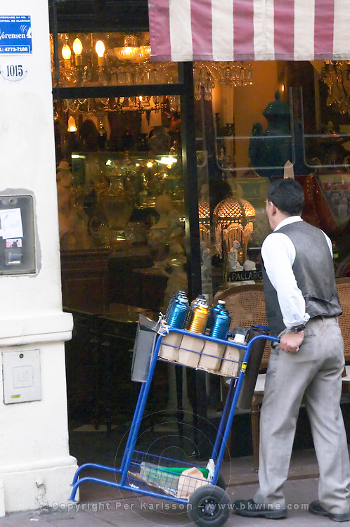 in the San Telmo district around Plaza Dorrego Square, a man walking from antique shop to shop selling on a hand pushed cart hot water from thermos flasks that will be used to make mate herbal tea. Calle Defensa Defence street Buenos Aires Argentina, South America