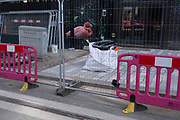 Painted flamingo hiding behind fencing and barriers on 31st March 2021 in Birmingham, United Kingdom. This is the area along Broad Street where a major redevelopment is taking place.