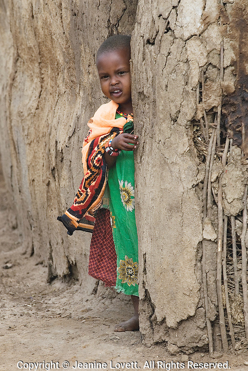 Masi girl peaks out her mud hut.