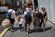 Street scene with passing tourists holding a large multi-coloured sphere and young Chinese women in Chinatown in Soho, London, United Kingdom. The present Chinatown is in the Soho area occupying the area in and around Gerrard Street. It contains a number of Chinese restaurants, bakeries, supermarkets, souvenir shops, and other Chinese-run businesses and is in itself a major tourist destination.