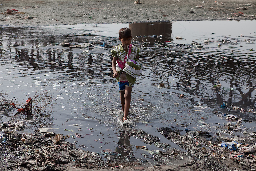 A young Indian girl is crossing the heavily polluted and semi-dry Yamuna River next to the Taj Mahal, in Agra.
