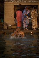 A pilgrim taking a holy bath in the River Ganges during the festival of Kartik Poornima in Varanasi, Uttar Pradesh, India