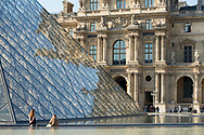 A woman poses for a photographer outside the glass pyramid at the Louvre Museum in Paris, France