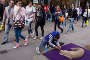Onlookers take interest in a street artist as he puts the finishing touches to a dog made from sand in central London.