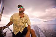 A man drives a boat across the coastal waters of North Carolina