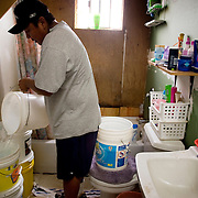 """In the bathroom of the Whitehair home, Greyhatt fills bucket after bucket with water used for daily grooming.  Homes are built with modern conveniences in hopes that one day they will have running water.  The Bureau of Reclamation estimated that the total economic cost to haul water on the reservation is about $113 per 1,000 gallons.  A Phoenix homeowner pays about $5 a month for as much as 7,480 gallons.  """"We're talking about things a lot of people take for granted,"""" said Ray Benally, director of the tribe's water resources department. """"It's about our quality of life. The lack of clean, potable water has an effect on people's health."""""""