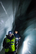 Glaciologist Nick Hulton (front) and a dog sled guide explore an ice cave in Scott Turnerbreen, Svalbard.