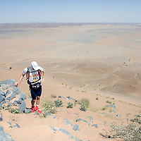 26 March 2007:  #505 Eric Deshaies of Canada rests as he reaches summit of jebel El Otfal, 947 meters and an average 25% slope, during the second stage (21.7 miles) of the 22nd Marathon des Sables between Khermou and jebel El Otfal. The Marathon des Sables is a 6 days and 151 miles endurance race with food self sufficiency across the Sahara Desert in Morocco. Each participant must carry his, or her, own backpack containing food, sleeping gear and other material.
