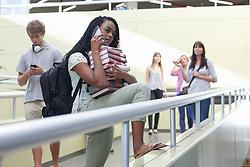 Female student on smartphone holding pile of books (Credit Image: © Image Source/Albert Van Rosendaa/Image Source/ZUMAPRESS.com)