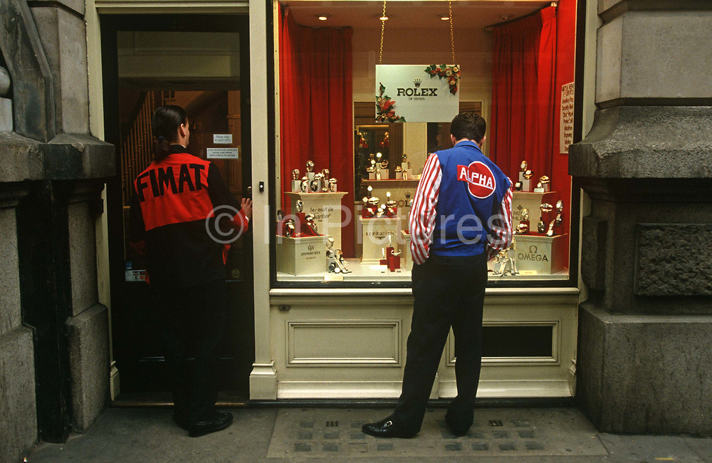 Two futures traders from the nearby LLIFE exchange shop for expensive Rolex watches during their lunchtimes in the City of London. Wearing the colourful jackets synonymous with the aggressive trading on the Futures market floor, two young men both admire the Rolex and Omega watches on display in this shop in the heart of the capital's financial district. The LIFFE exchange was synonymous with Thatcherite capitalist moneymaking ethos in the City of London of the 80s and early 90s before the takeover by Euronext in January 2002. It is currently known as Euronext.liffe. Euronext subsequently merged with New York Stock Exchange in April 2007.
