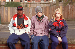 Multiracial group of youths sitting on brick wall looking serious,