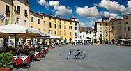 Outdoor cafe's in the Piazza dell'Anfiteatro inside the ancinet Roman ampitheatre of Lucca, Tunscany, Italy . Piazza dell'Anfiteatro is a public square in the northeast quadrant of walled center of Lucca. The ring of buildings surrounding the square, follows the elliptical shape of the former second century Roman amphitheater of Lucca. The square can be reached through four gateways located at the four vertices of the ellipse. A cross is carved into the central tile of the square with the arms pointing to the four gateways of the square. The base of the former amphitheater  dating back to the 1st or 2nd century BC, at its peak had about 18 rows of amphitheater seats held some 10,000 spectators.<br /> <br /> Visit our ITALY HISTORIC PLACES PHOTO COLLECTION for more   photos of Italy to download or buy as prints https://funkystock.photoshelter.com/gallery-collection/2b-Pictures-Images-of-Italy-Photos-of-Italian-Historic-Landmark-Sites/C0000qxA2zGFjd_k<br /> .<br /> <br /> Visit our ROMAN ART & HISTORIC SITES PHOTO COLLECTIONS for more photos to download or buy as wall art prints https://funkystock.photoshelter.com/gallery-collection/The-Romans-Art-Artefacts-Antiquities-Historic-Sites-Pictures-Images/C0000r2uLJJo9_s0 If you prefer to buy from our ALAMY PHOTO LIBRARY  Collection visit : https://www.alamy.com/portfolio/paul-williams-funkystock/lucca.html .