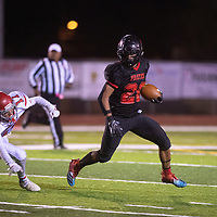 Isiah Johnson (20) carries the ball for Grants Pirates as  Bernalillo Spartans' Jamielee Long (17) tries to defend Friday night in Grants. The Pirates beat the Spartans 44-0.