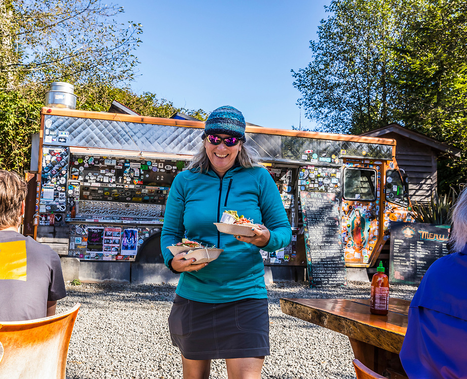 A happy smiling woman carrying food to the tables at Tacofino in Tofino, BC, Canada.