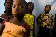 Alice Bienvenue Djaha Aya, 7, (front) and her mother Viviane M'Bra Affoue, 32, (left) at their family home in Dimbokro, Cote d'Ivoire on Friday June 19, 2009. Both are HIV-positive. Other children are not members of the family.