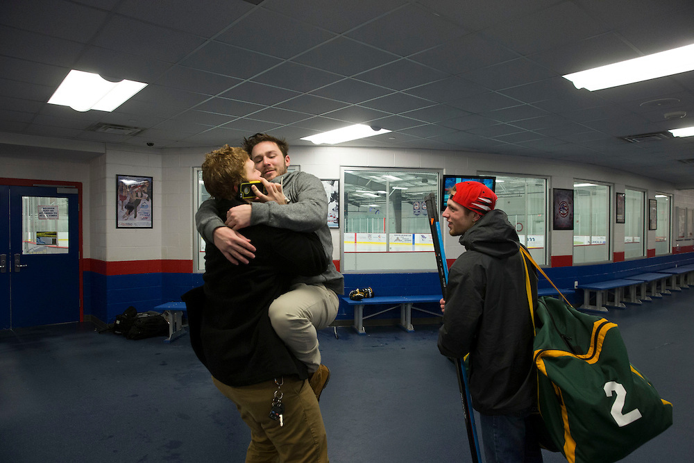 George Mason defenseman, Alex Mandeville, (L) talks on the phone with his girlfriend after practice while forward, Brian Bock, (C) and goalie, Nick Wayland, (R) try to distract him at at Prince William Ice Rink in Woodbridge, VA on January 22, 2014.