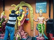 05 JUNE 2015 - KUALA LUMPUR, MALAYSIA:  An attendant in a Hindu shrine in the Little India section of Kuala Lumpur hangs flower garlands on a deity.    PHOTO BY JACK KURTZ