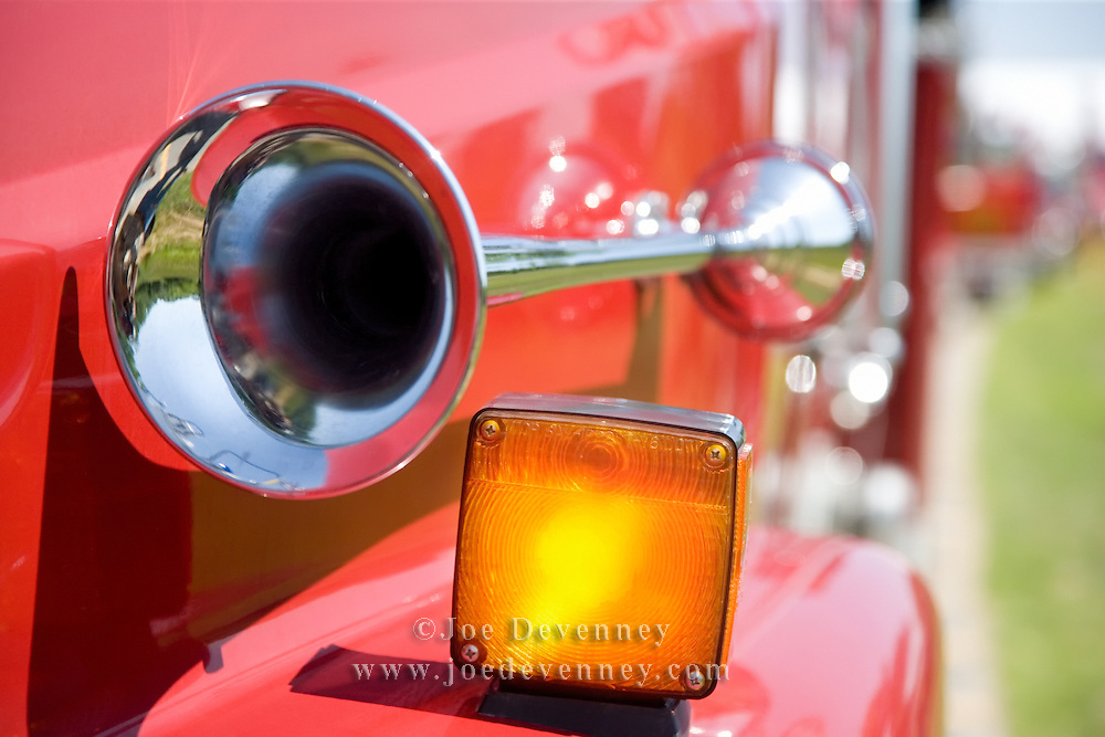 Siren and turn signal light on the fender of a red fire truck