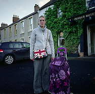 "'Woman with a Union Jack bag, Town Yetholm, 2014' from 'A Fine Line - Exploring Scotland's Border with England' by Colin McPherson.<br /> <br /> A woman with a Union Jack bag waiting for a bus before going to nearby Kelso to shop. ""People think the bag represents my politics, but really, I just liked it'"" she said.<br /> <br /> The project was a one-year exploration of the border between the two historic nations, as seen from the Scottish side of the frontier.<br /> <br /> Colin McPherson is a photographer and visual artist based in north west England. In 2012 he was one of the founding members of Document Scotland, a collective of four Scottish documentary photographers brought together by a common vision to witness and photograph the important and diverse stories within Scotland at one of the most important times in our nation's history.<br /> <br /> 'A Fine Line' will be shown for the first time in public at Impressions Gallery, Bradford, from July 1 until September 27, 2014 to coincide with the Scottish Independence referendum."
