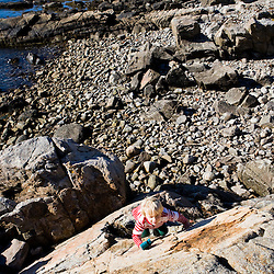 A boy (age 4) climbs a rock on the coast in Biddeford, Maine. Timber Point.