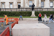 A work contractor cleans paving stones alongside a pointing statue of King James II (as Roman Emperor) in Trafalgar Square, on 14th October, 2021, in Westminster, London, England.