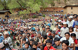 "RUKUM DISTRICT, NEPAL, APRIL 22, 2004: Villagers watch as Maoist insurgents celebrate in Rukum district April 22, 2004 weeks after their attack on government troops in Beni when they overran the district headquarters, looting a bank, destroying the jail and torching government office buildings. The government said that 32 security personnel died in the clash and 37 were kidnapped. The clash was one of the deadliest since 1996 when fighting began to topple the constitutional monarchy and install a communist republic. The guerrillas' strength is hard to gauge. Analysts and diplomats estimate there about 15,000-20,000 hard-core fighters, including many women, backed by 50,000 ""militia"".  In their remote strongholds, they collect taxes and have set up civil administrations, and ""people's courts"" to settle rows. They also raise money by taxing villagers and foreign trekkers. Though young, they are fearsome fighters and  specialise in night attacks and hit-and-run raids. They are tough in Nepal's rugged terrain, full of thick forests and deep ravines and the 150,000 government soldiers are not enough to combat this growing movement that models itself after the Shining Path of Peru. (Ami Vitale/Getty Images)"