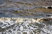 Breaking waves in choppy murky brown sea water carrying heavy sediment load, Dovercourt, Harwich, Essex, England