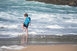 A young boy playing at Fistral Beach in Newquay, Cornwall.