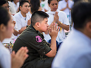 23 NOVEMBER 2014 - BANGKOK, THAILAND: A military cadet prays at a mass alms giving ceremony in Bangkok Sunday. 10,000 Buddhist monks participated in the ceremony on Rajadamri Road in front of Central World shopping mall. The alms giving was to assist Buddhist temples in the insurgency wracked southern provinces of Thailand, where Buddhist monks on their alms rounds have been targeted by Muslim extremists. The ceremony was sponsored by Wat Phra Dhammakaya, the center of the Dhammakaya Movement, a Buddhist sect founded in the 1970s. The temple has become active in Thai politics.    PHOTO BY JACK KURTZ
