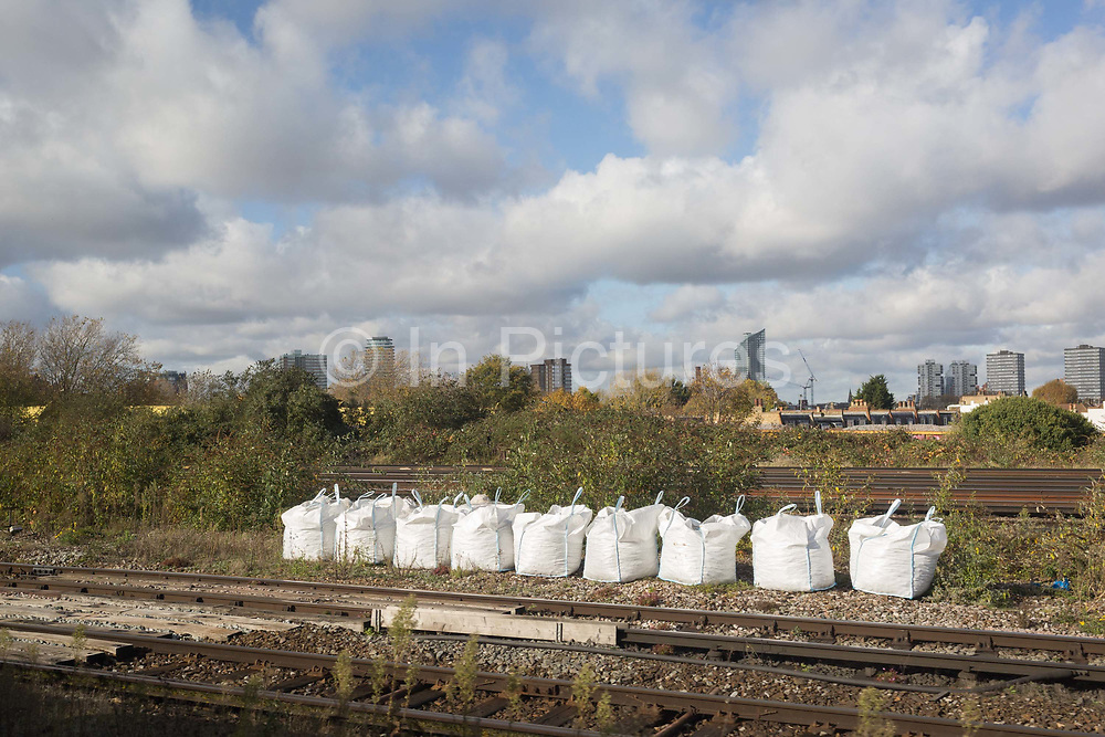Aggregates and construction materials lined up at the trackside, seen through the window of a Southern train carriage window, on 7th November 2019, in London, England.