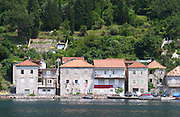Stone houses along the water edge in Lepetani. Montenegro, Balkan, Europe.