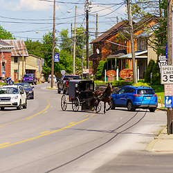 Intercourse, PA, USA / May 30, 2020: An Amish buggy travels through the village in rural Lancaster County.