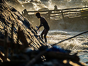 18 JUNE 2016 - DON KHONE, CHAMPASAK, LAOS: A fisherman with his catch climbs the rocks on shore at  Khon Pa Soi Waterfalls, on the east side of Don Khon. It's the smaller of the two waterfalls in Don Khon. Fishermen have constructed an elaborate system of rope bridges over the falls they use to get to the fish traps they set. Fishermen in the area are contending with lower yields and smaller fish, threatening their way of life. The Mekong River is one of the most biodiverse and productive rivers on Earth. It is a global hotspot for freshwater fishes: over 1,000 species have been recorded there, second only to the Amazon. The Mekong River is also the most productive inland fishery in the world. The total harvest of fish from the Mekong is approximately 2.5 million metric tons per year. By some estimates the harvest in the Tonle Sap (in Cambodia) had doubled from 1940 to 1995, but the number of people fishing the in the lake has quadrupled, so the harvest per person is cut in half. There is evidence of over fishing in the Mekong - populations of large fish have shrunk and fishermen are bringing in smaller and smaller fish.        PHOTO BY JACK KURTZ
