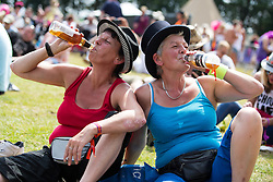 © Licensed to London News Pictures . 08/08/2015 . Siddington , UK . Two women drinking beer in the sunshine . The Rewind Festival of 1980s music , fashion and culture at Capesthorne Hall in Macclesfield . Photo credit: Joel Goodman/LNP