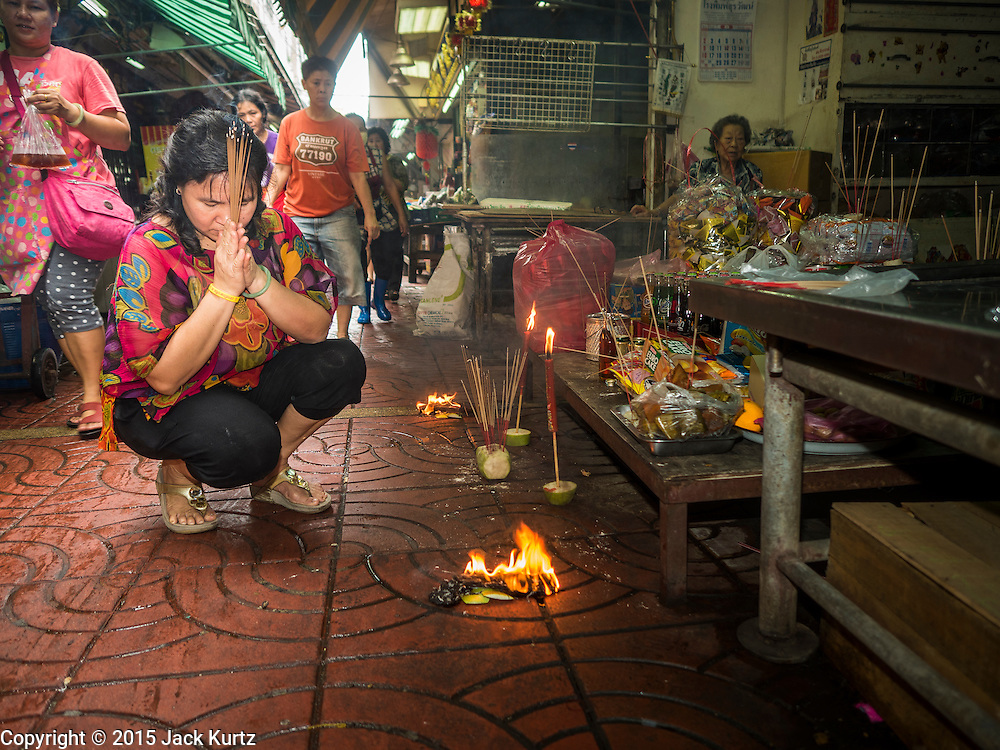 """28 AUGUST 2015 - BANGKOK, THAILAND: A woman prays and burns """"ghost money"""" for her ancestors on Hungry Ghost Day in Bangkok's Chinatown. Mahayana  Buddhists believe that the gates of hell are opened on the full moon of the seventh lunar month of the Chinese calendar, and the spirits of hungry ghosts allowed to roam the earth. These ghosts need food and merit to find their way back to their own. People help by offering food, paper money, candles and flowers, making merit of their own in the process. Hungry Ghost Day is observed in communities with a large ethnic Chinese population, like Bangkok's Chinatown.        PHOTO BY JACK KURTZ"""